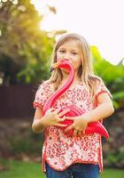 portret van schattig klein meisje buiten met roze flamingo foto