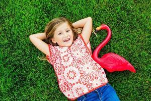 glimlachend meisje dat op groen gras met roze flamingo ligt foto