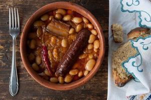 gebakken bonen met worst, geserveerd in een kleischotel