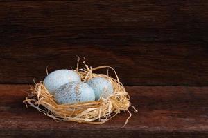 Pasen raffia nest eend eieren op ruwe achtergrond foto