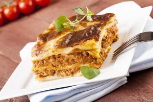 deel van smakelijke lasagne op een bord foto