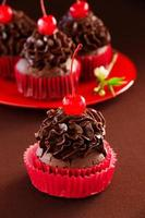 verse chocolademuffins met chocoladeroom en kersen. foto