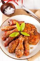 zelfgemaakte gerookte kip drumsticks en dijen op een bord foto