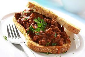 close-up van een sandwich rundvlees geserveerd op een witte plaat foto