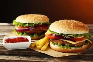 afbeelding van 2 hamburgers op een houten tafel met friet en ketchup