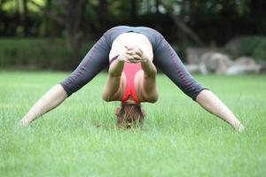 leuke jonge vrouw die fysieke oefeningen op gazon doet foto