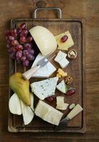 kaasplank met diverse soorten kaas (parmezaan, brie, blauw, cheddar) foto