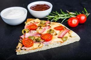stuk pizza met ham en tomaten foto