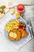 schnitzel met frietjes en een pittige dip foto