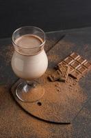 glas chocolade milkshake op tafel foto