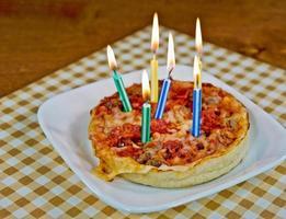 verjaardagskaarsen op een pizza foto