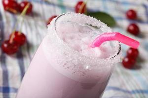 melk cocktail met een kers in een glas macro. horizontaal foto