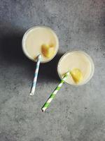 zelfgemaakte Piña Colada in twee glazen met gestreepte papieren rietjes foto