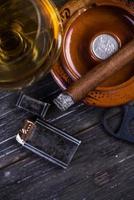 Cubaanse sigaar in asbak, glas rum op tafel foto