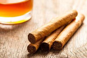 Cubaanse sigaren op houten tafel met glas rum