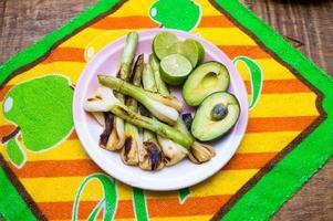 gegrilde uien, gesneden avocad en limoenen foto