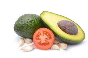 verse avocado omgeven door tomaat, knoflook en limoen foto