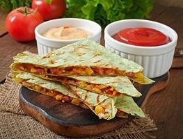 Mexicaanse quesadilla gesneden met groenten en sauzen