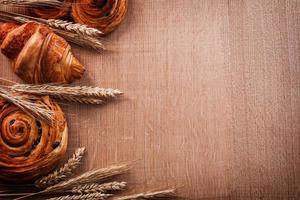 samenstelling van tarwe oren bakkerijproducten op eiken houten bord foto