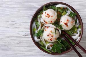 Aziatische soep met visballetjes en rijstnoedels bovenaanzicht