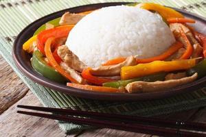 Chinese rijst met kip en groenten close-up op een plaat