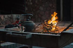 het verwarmen van de thee boven het vuur foto