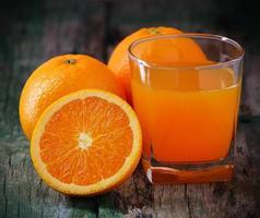 jus d'orange glas en verse sinaasappelen op hout foto