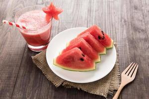 gezonde plak watermeloen met watermeloen smoothie op een houten rug foto