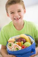 jonge jongen die lunchpakket houdt foto