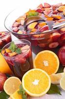 een schaal met fruitpunch omgeven door fruit foto