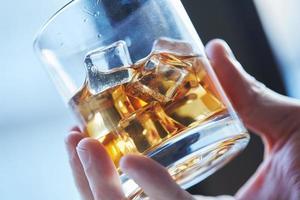 glas whisky met ijs in zijn hand foto