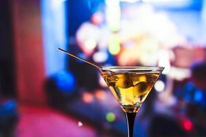 glas met martini en groene olijven foto
