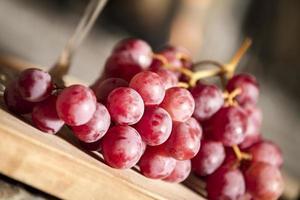 rode wijndruiven over een houten tafel foto