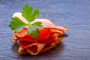 gekrulde plakjes heerlijke prosciutto met peterselieblaadjes foto