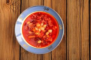 portie zelfgemaakte Russische rode bietensoep borsch met bonen foto