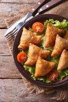 gebak samosa's op een plaat close-up. verticaal bovenaanzicht, rustiek foto
