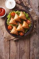 samosa op plaat met saus, verticale bovenaanzicht foto
