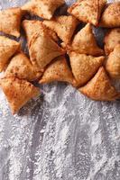 stapel bakken samosa's op bebloemde tafel. verticaal bovenaanzicht