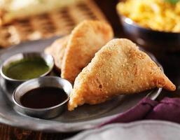 plaat van Indiase samosa met munt en hete chutney foto