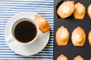 zelfgemaakte madeleine koekjes in ovenschaal, koffiekopje foto