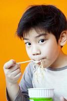Aziatische schattige jongen met noodle cup