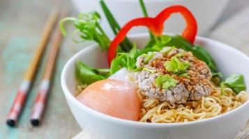 Chinese noedels met gehakt varkensvlees en ei in kom foto