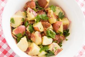 aardappelsalade gemaakt met nieuwe rode aardappelen en spek van kalkoen foto