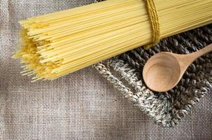 spaghetti ongekookt en lepel hout in mand op jute foto