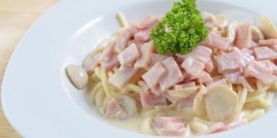 spaghetti carbonara met ham en champignons op witte schotel foto