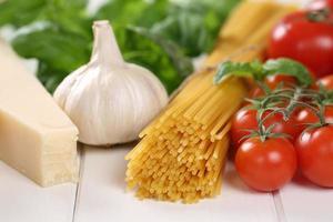 ingrediënten voor een spaghetti pasta noodles maaltijd met tomaten, basilicum foto