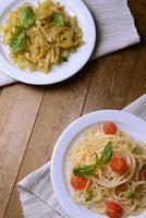 heerlijke spaghetti met tomaten op plaat op tafel close-up foto