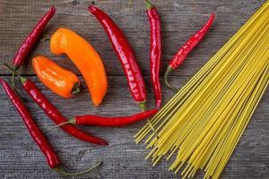 rode peper en spaghetti op oude houten tafel foto