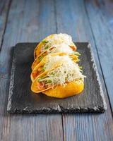 Mexicaanse taco's met vlees, bonen, avocado, kaas en tomatensaus foto