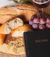 heilige bijbel tegen een setting van communiebrood en wijn foto